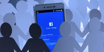 paper cutouts holding hands around a phone with the facebook app displayed