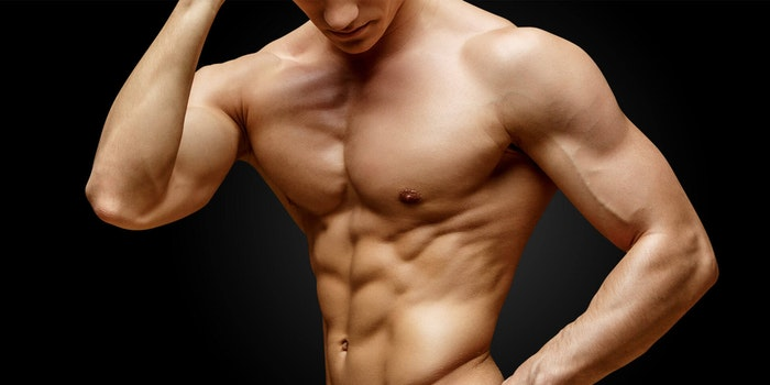 Male bodybuilder posing over black background