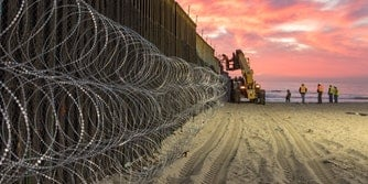 U.S. Border Patrol Agents in San Diego seen behind barbed wires at the border