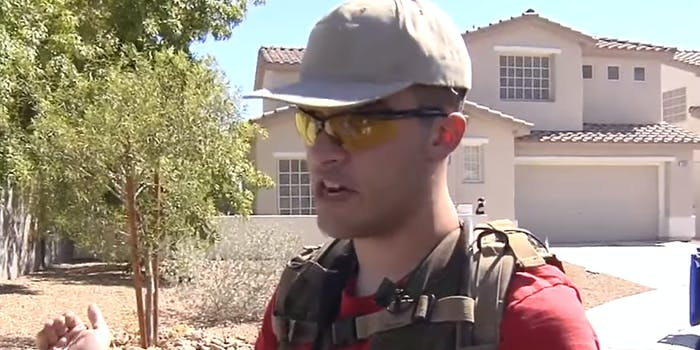 armed conor climo stands in front of neighbors house