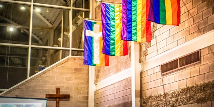 LGBTQ flags seen at a church in front of a Cross