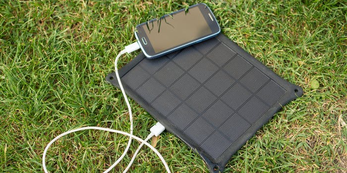phone plugged into solar charger on grass
