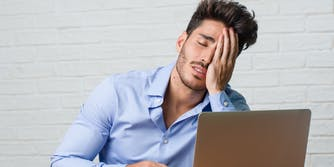 exasperated man with hand on face in front of laptop