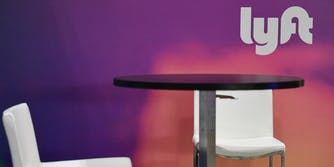 A Lyft sign is seen behind a table and two empty chairs