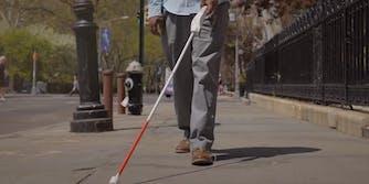 man using wewalk smart cane to navigate street
