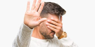 man covering eyes, placing hand up to stop