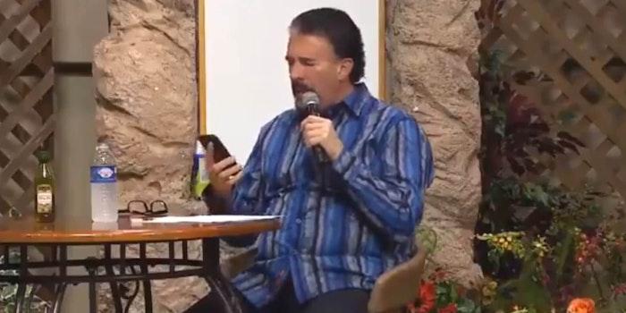 Perry Stone Jr pretending to speak in tongues as he checks his phone