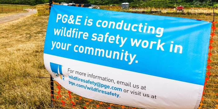 """pg&e is conducting wildfire safety work in your community"" sign on construction fencing"