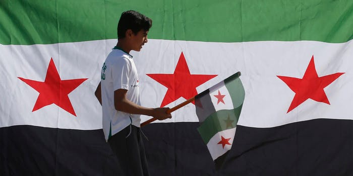 Syrian youth holds revolutionary flag in front of Syrian flag