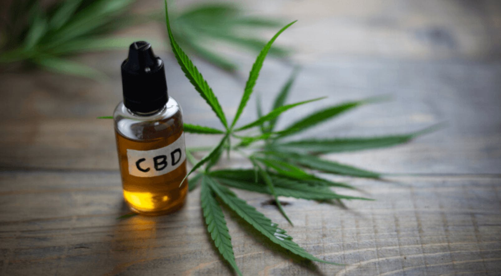 A bottle of CBD oil next to a cannabis leaf