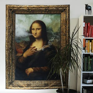 Picture of the Stona Lisa tapestry (an image of the Mona Lisa that's been edited to make it look like she is holding and smoking a joint) hanging on a wall next to a bookshelf.