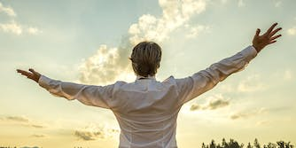 man in dress shirt raising his hands to the sky