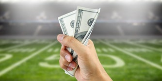 Person holding cash in front of football field