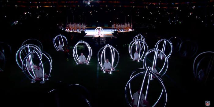 Children in a a sea of oval shaped carriages illuminated with white cage-like borders