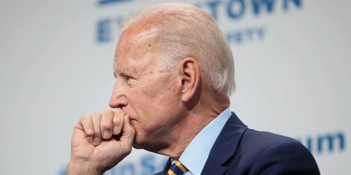 Joe Biden holding his fist up to his mouth