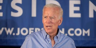 Joe Biden standing in front of a campaign banner