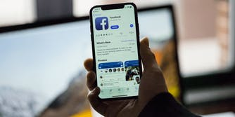 A hand holding up a cellphone with the Facebook app on it