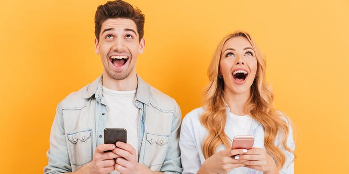 man and woman laughing at jokes on their phones