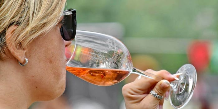 A woman with short blonde hair drinking from a wine glass