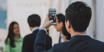 A man taking a picture of people with his cell phone
