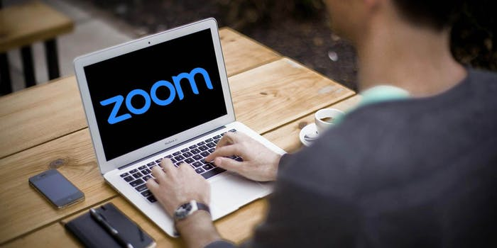 A man sitting in front of a laptop with the Zoom logo