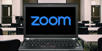 A laptop with the word zoom on its screen in a classroom