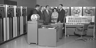 A group of people standing in front of computers from the 1960s