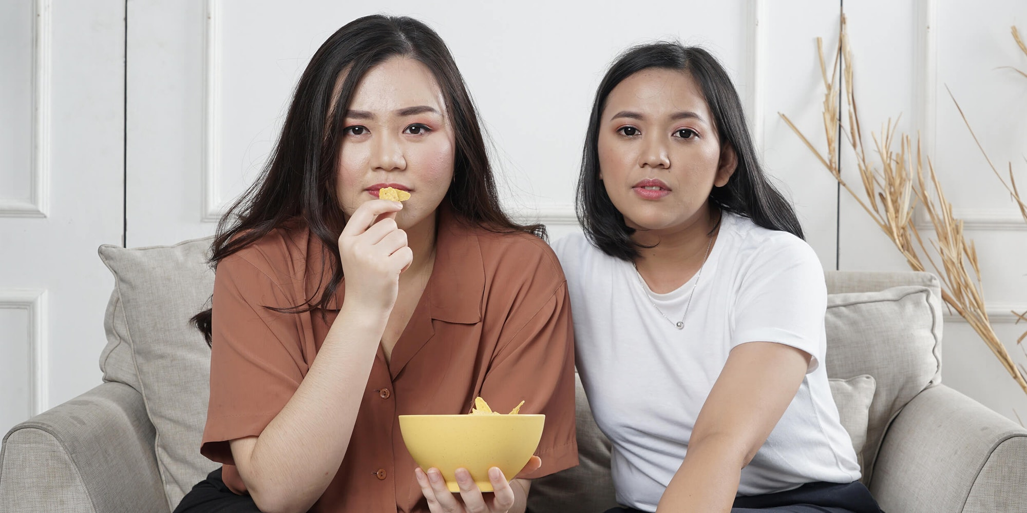 women sitting on couch eating chips