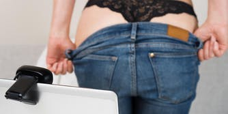 woman taking off her jeans in front of a webcam
