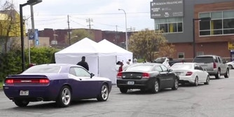 Cars lined up outside of two white tents