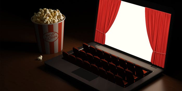 movie theater seats in place of keyboard on laptop, screen has red curtains opening