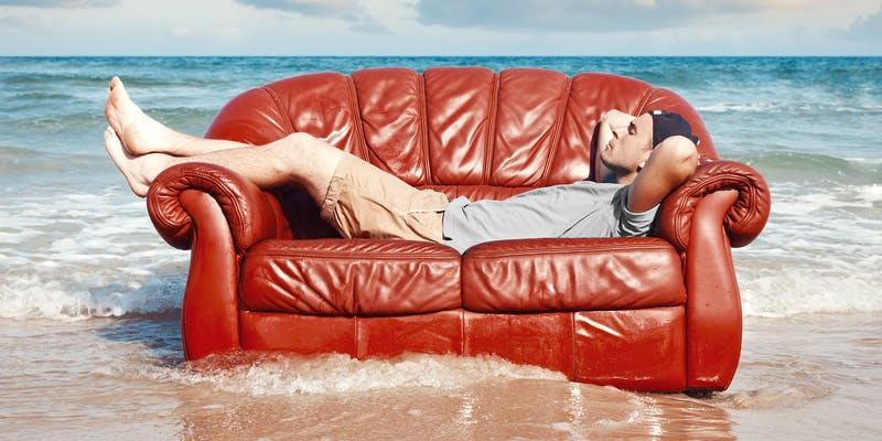man laying on couch in the surf
