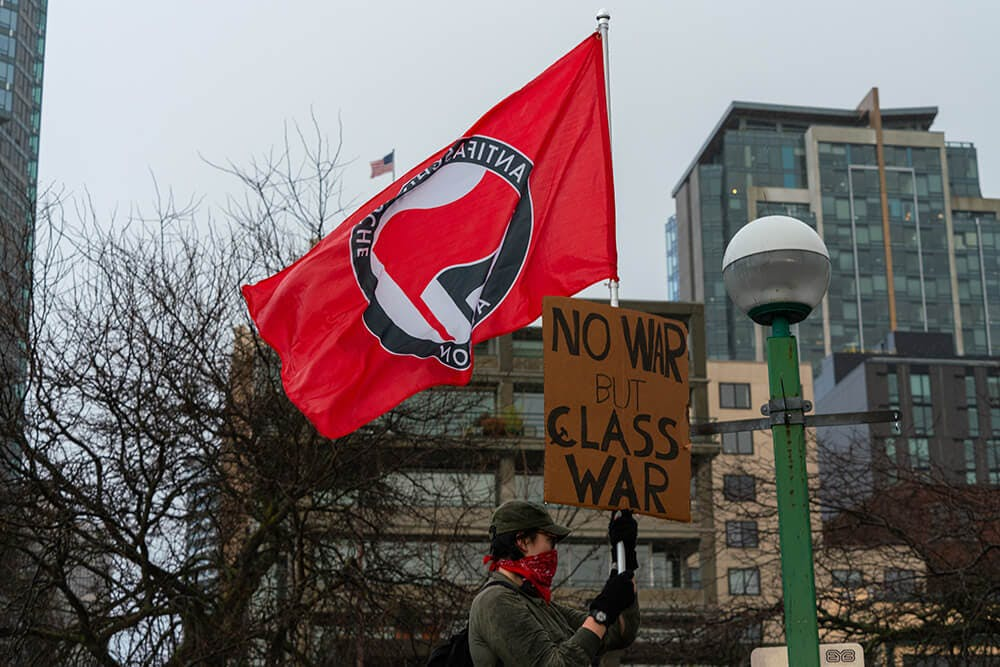"""protester holds antifacist flag and """"no war but class war"""" sign"""