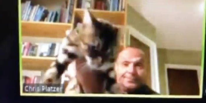 Chris Platzer holding up his cat during a zoom meeting