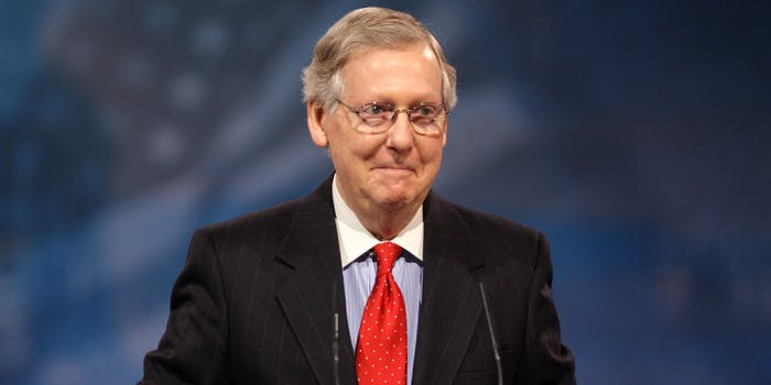 Mitch McConnell standing in front of American flag