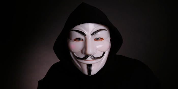 A man wearing a Guy Fawkes mask associated with Anonymous