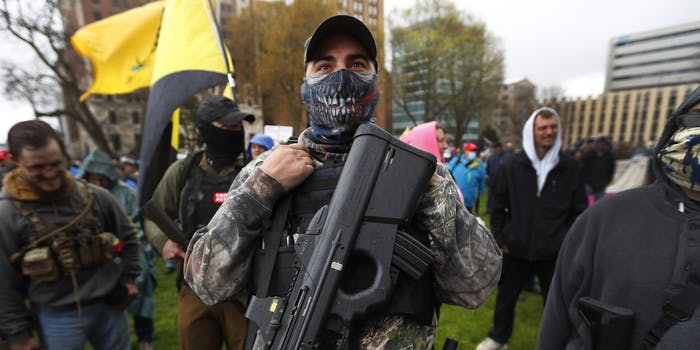 Protester carries his rifle at the State Capitol in Lansing, Mich.,