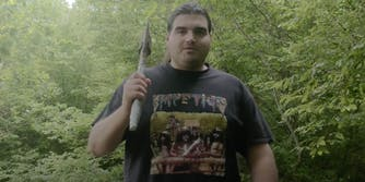 A Bosnian YouTuber holding an axe in the woods