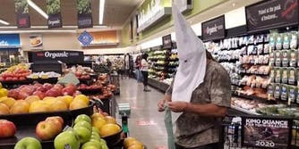 A man wearing a KKK hood while grocery shopping