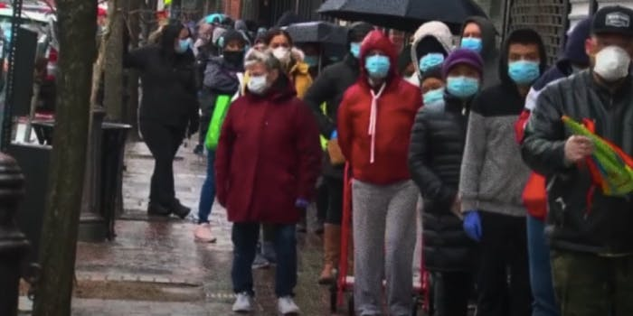 people waiting in line with face masks on