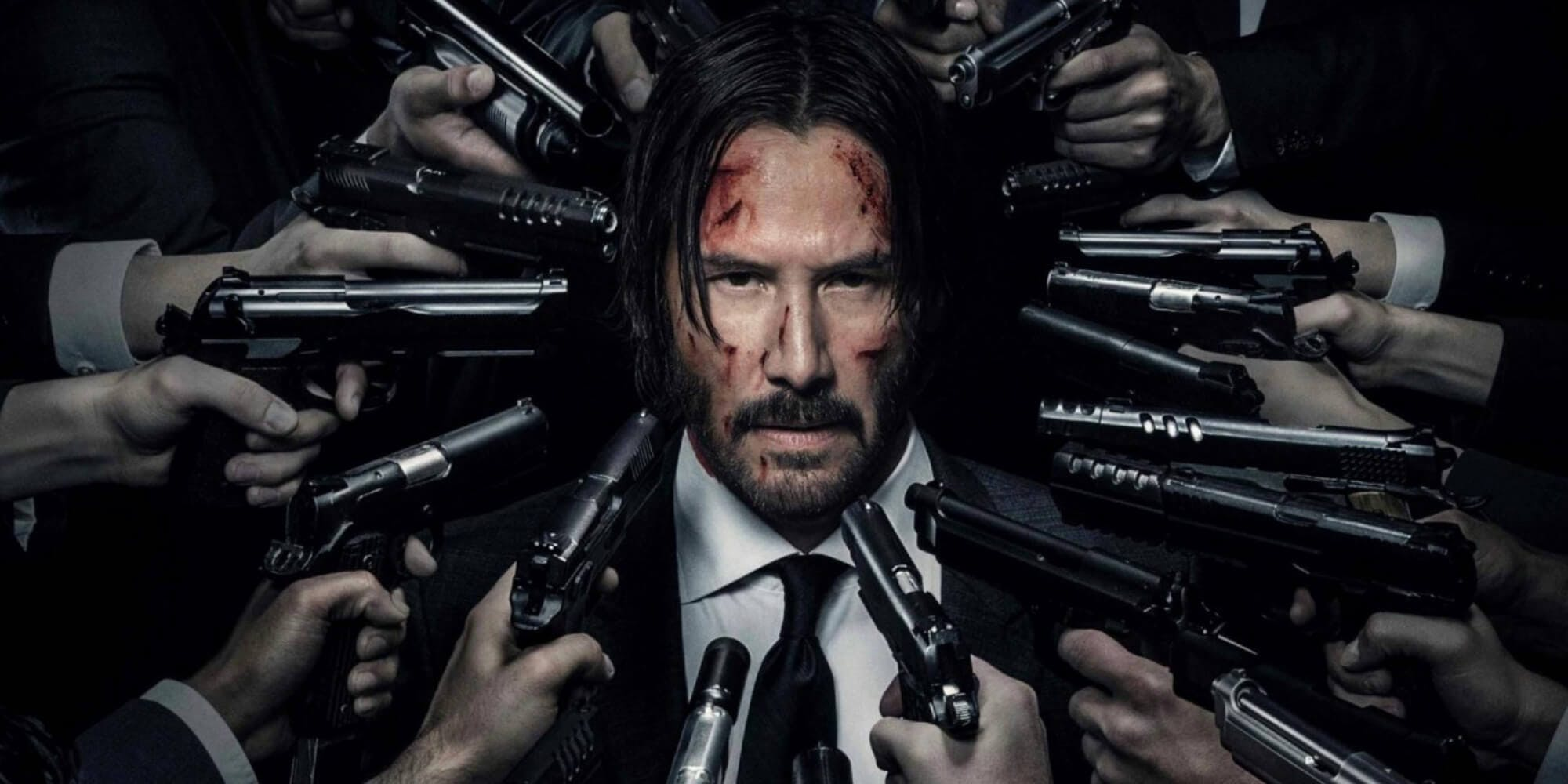 Photo of the movie John Wick where Keanu Reeves is surrounded by bad guys pointing guns at his face.