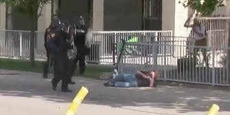 An old man laying on the pavement next to cops in riot gear