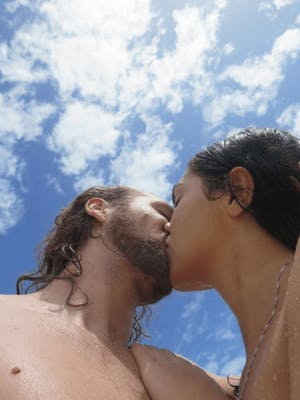 Image of couple kissing under the blue sky