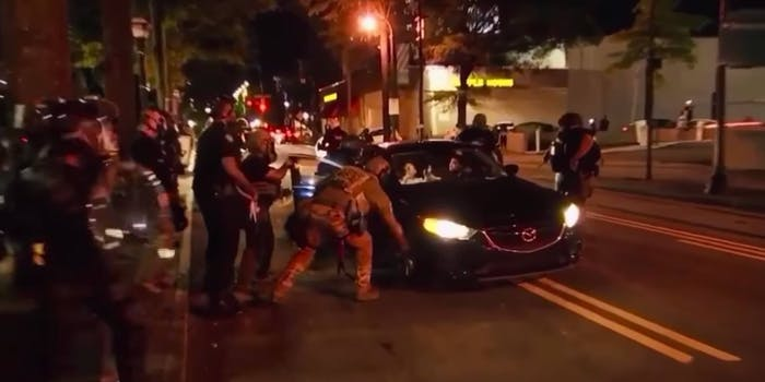 Screengrab shows about a dozen cops swarming the scene where cops attacked two college students