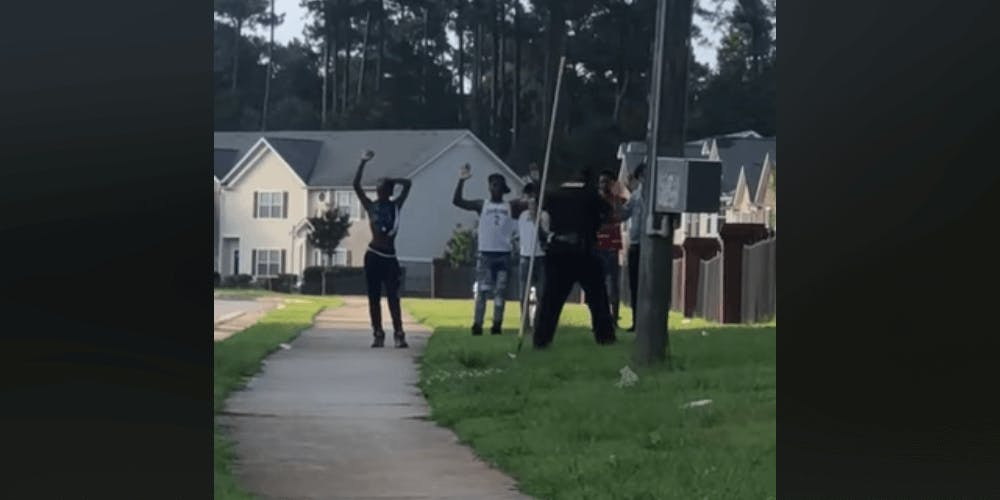 Screenshot of a video of six black teens with their hands in the air while a cop holds a gun on them