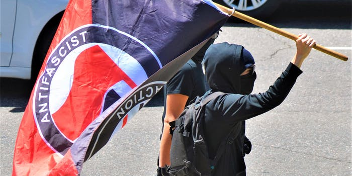 person carrying Antifascist Action flag