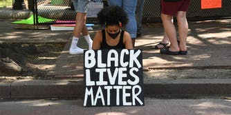woman sitting on curb holding a Black Lives Matter sign, wearing a facemask