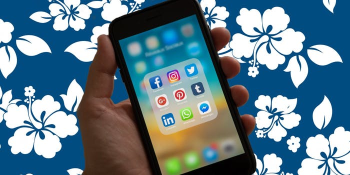 A phone with social media apps over a Hawaiian shirt pattern