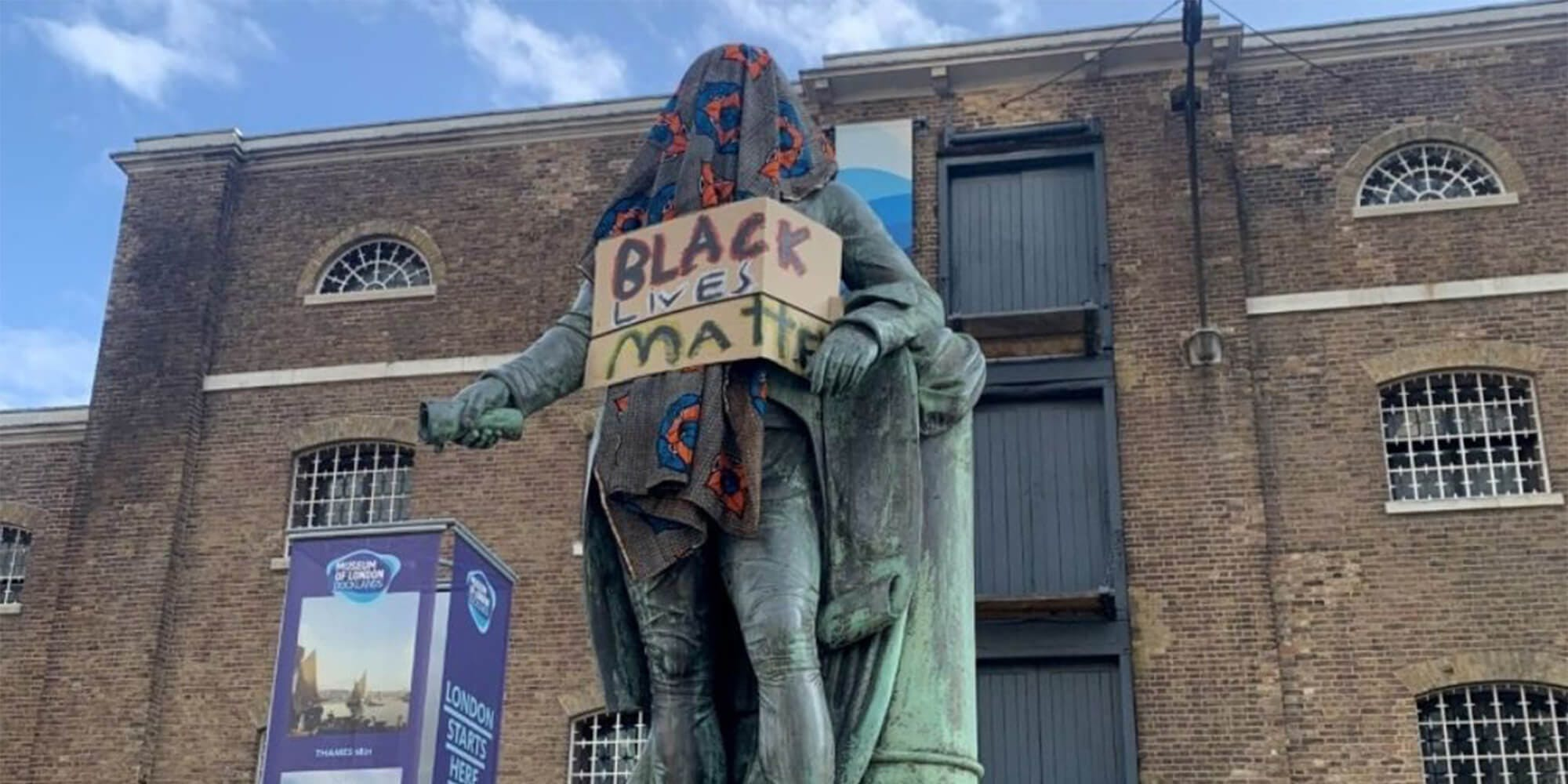 "robert milligan statue covered with blanket and ""Black Lives Matter"" sign"