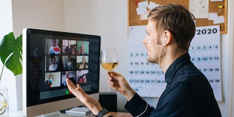 man holding glass of wine on zoom call